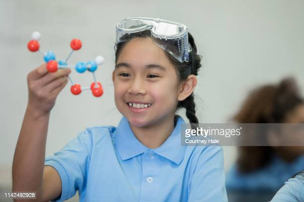 junior high school girl enjoying stem science class and examining a molecule model - charter_school stock pictures, royalty-free photos & images