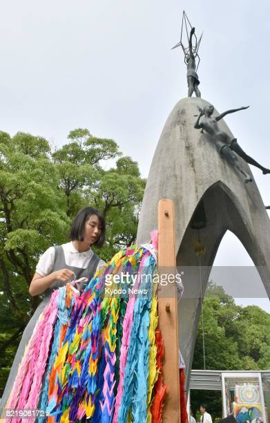 Junior high school student offers paper cranes, a symbol of hope in Japan, at the Children's Peace Monument in the Hiroshima Peace Memorial Park in...