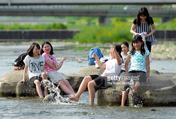 Junior high school students enjoy bathing their feet at Kamogawa River on May 9 2013 in Kyoto Japan Covered by a high pressure cities in Japan record...