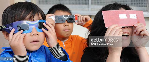 Junior high school students observe the annular solar eclipse through special glasses at the playground of their school in Kawakaki surburban Tokyo...