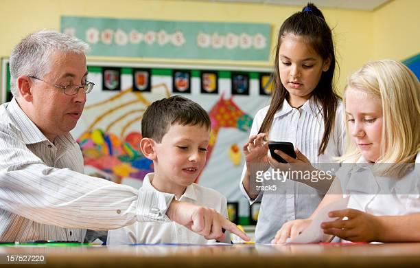 Junior high school teacher helping kids with math in class.