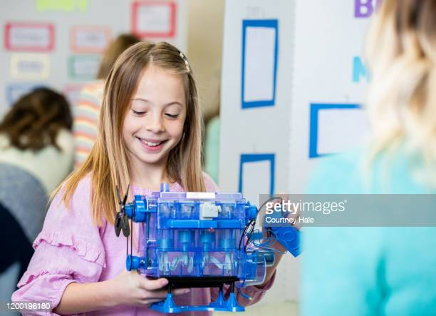 junior high student explaining how her model motor works - junior girl models stock pictures, royalty-free photos & images