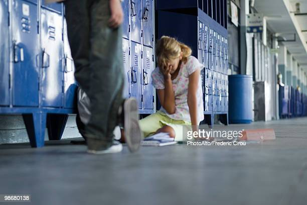 junior high student sitting on floor crying, boy standing by watching - bullying escolar fotografías e imágenes de stock