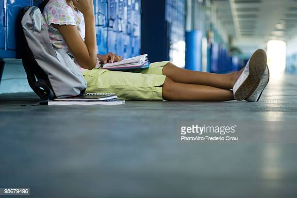 Junior high student sitting on hall floor leaning against lockers reading book