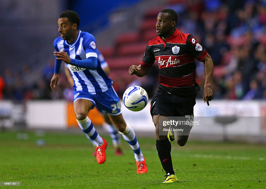 Junior Hoilett of Queens Park Rangers beats James Perch of Wigan Athletic during the Sky Bet Championship Play Off Semi Final first leg match between Wigan Athletic and Queens Park Rangers at DW Stadium on May 9, 2014 in Wigan, England.