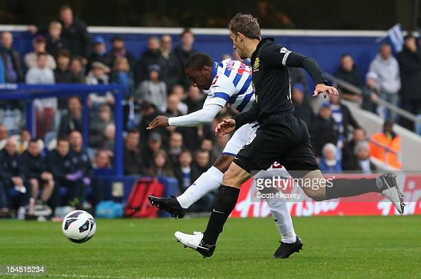 Junior Hoilett of Queens Park Rangers shoots past Phil Neville of Everton to score their first goal during the Barclays Premier League match between...