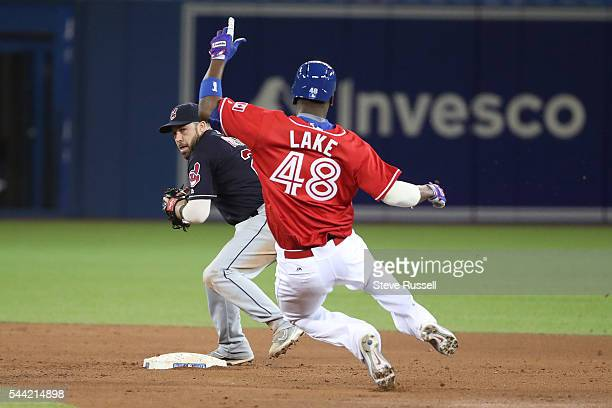 Junior Lake breaks top a double play as the Toronto Blue Jays lose the Cleveland Indians 2-1 in 19 innings on Canada Day at the Rogers Centre in...