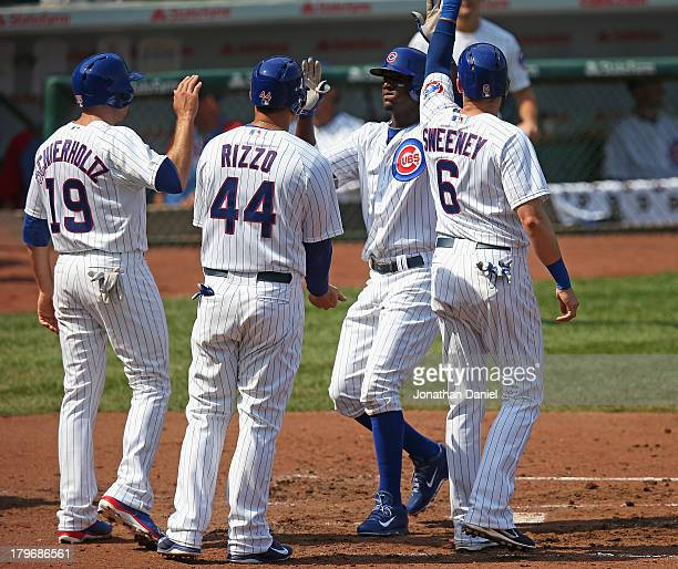 Junior Lake of the Chicago Cubs is greeted at home plate by teammates Nate Schierholtz Anthony Rizzo and Ryan Sweeney after hitting a grand slam home...