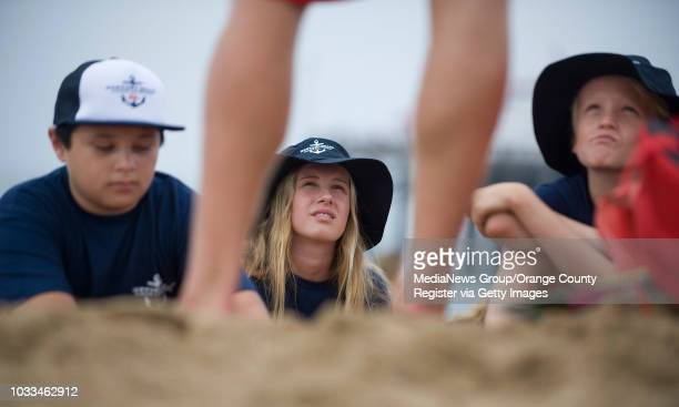 Junior Lifeguards Matthew Osborne from left Mary Jones and Charlie Jeffs listen to their instructor Matthew Peters during the first day of camp in...