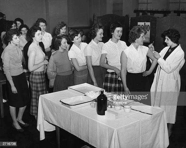 Junior members of staff at the Ministry of Health on Saville Row, London line up to receive their inoculation against polio, as part of a national...