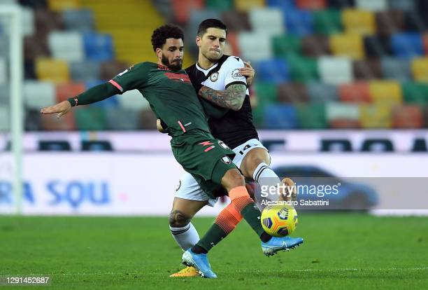 Junior Messias of FC Crotone competes for the ball with Kevin Bonifazi of Udinese Calcio during the Serie A match between Udinese Calcio and FC...