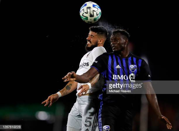 Junior Moreno of DC United and Victor Wanyama of Montreal Impact battle for a header during a Group C match as part of the MLS Is Back Tournament at...