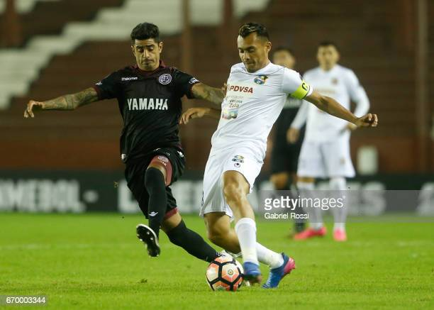 Junior Moreno of Zulia fights for the ball with Roman Martinez of Lanus during a group stage match between Lanus and Zulia as part of Copa CONMEBOL...
