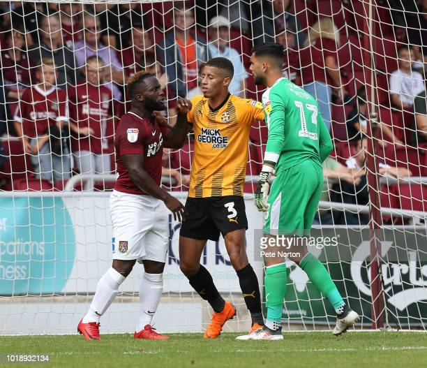 Junior Morias of Northampton Town clashes with Dimitar Mitov of Cambridge United as Jake Carroll intervenes during the Sky Bet League Two match...