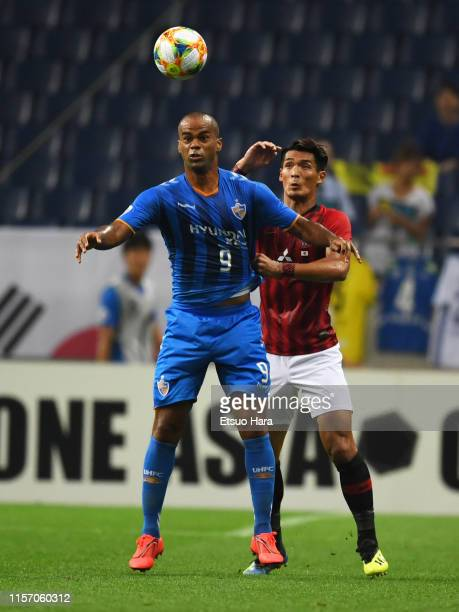 Junior of Ulsan Hyundai and Tomoaki Makino of Urawa Red Diamonds compete for the ball during the AFC Champions League round of 16 first leg match...