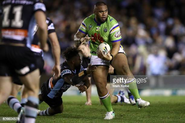 Junior Paulo of the Raiders breaks the tackle of James Segeyaro of the Sharks during the round 22 NRL match between the Cronulla Sharks and the...