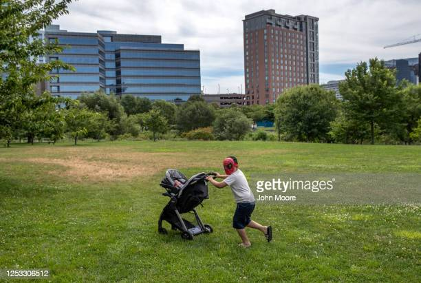 Junior pushes his brother Neysel 10 weeks through a park on June 25 2020 in Stamford Connecticut Junior and his parents Zully and Marvin survived...
