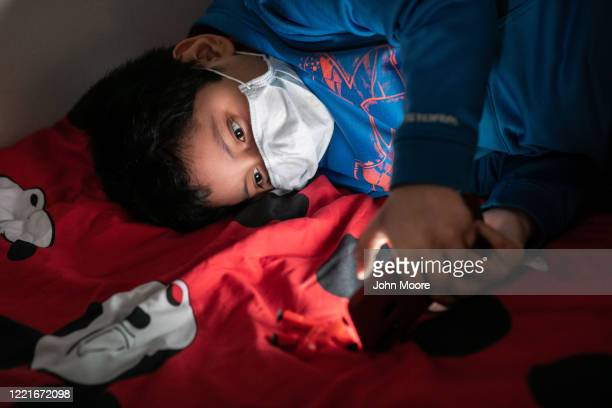 Junior recovering from COVID19 plays games on his father's phone on April 25 2020 in Stamford Connecticut He and his father were sick and quarantined...