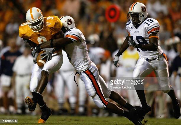 Junior Rosegreen of the Auburn Tigers tackles Bret Smith of the Tennessee Volunteers as Montavis Pitts watches during their game at Neyland Stadium...