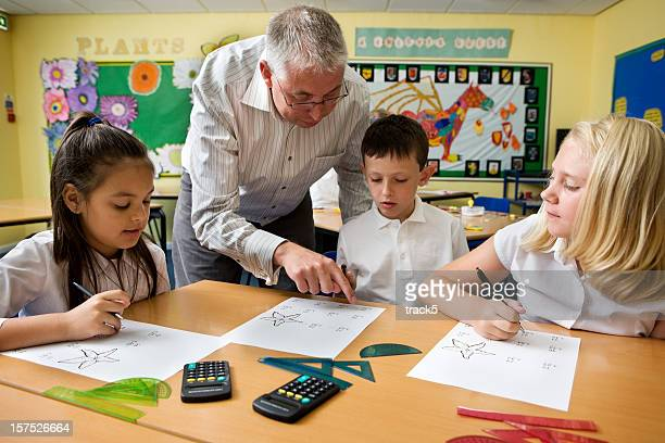 junior school: teacher helping his primary age pupils with maths