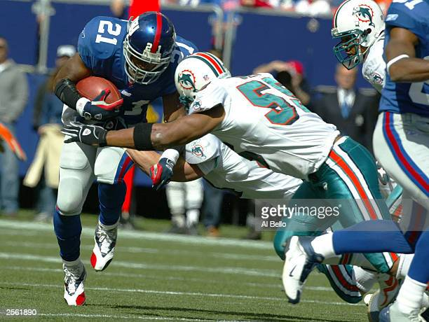 Junior Seau of the Miami Dolphins tackles Tiki Barber of the New York Giants during their game at Giants Stadium on October 5, 2003 in East...