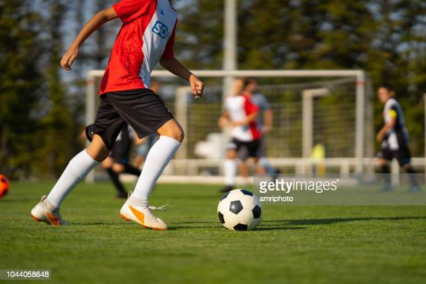 junior soccer player with football during match - grass court stock pictures, royalty-free photos & images