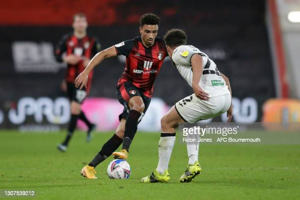 Junior Stanislas of Bournemouth is closed down by Joel Latibeaudiere of Swansea City during the Sky Bet Championship match between AFC Bournemouth...