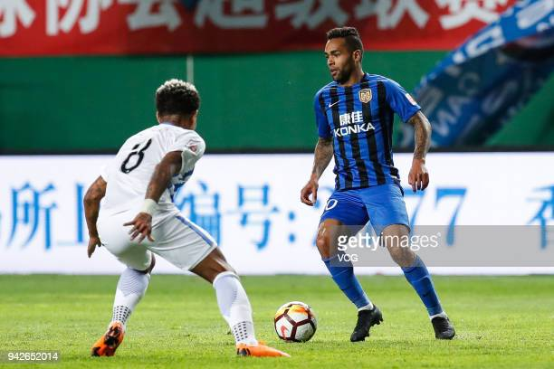 Junior Urso of Guangzhou RF and Alex Teixeira of Jiangsu Suning compete for the ball during the 2018 Chinese Super League match between Guangzhou RF...