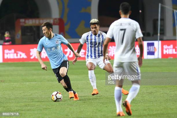 Junior Urso of Guangzhou RF and Zhou Ting of Dalian Yifang compete for the ball during the 2018 Chinese Football Association Super League second...