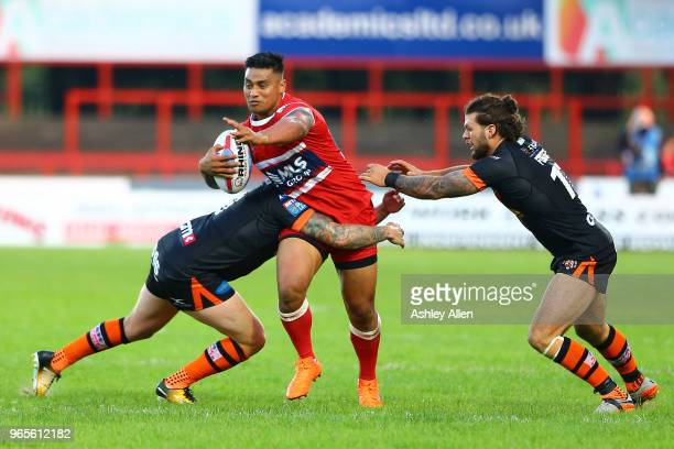 Junior Vaivai of Hull KR has his progress blocked by Jamie Ellis and Alex Foster of Castleford Tigers during the Roger Millward Trophy match between...