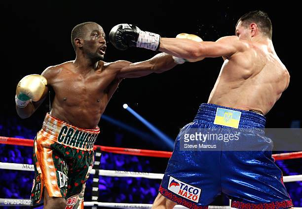 WBO junior welterweight champion Terence Crawford throws a punch at WBC champion Viktor Postol during their title unification fight at MGM Grand...