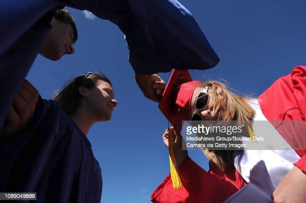 Juniors and graduation escorts Cody Walega, left, and Paige Huey, both 17, look at photos on senior Kayla Luhrs' cap before the start of the 2008...
