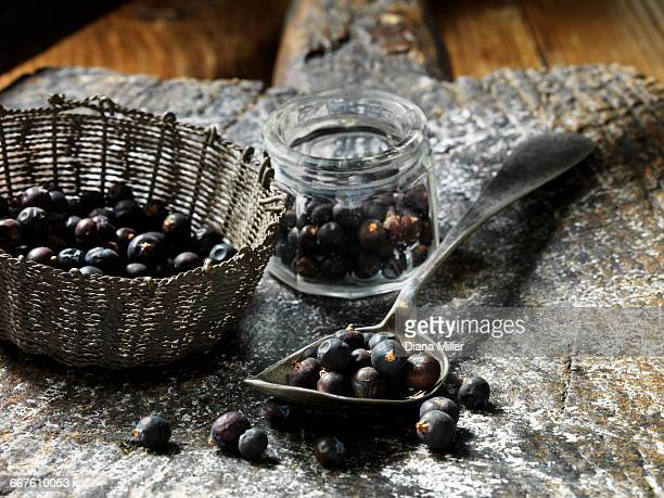 Juniper berries in small glass jar, metal vintage spoon and woven basket, rustic wooden chopping board