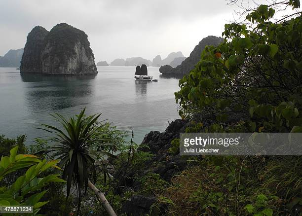 A junk anchors in Bai Tu Long Bay on April 18 2015 in Ha Long Bay Vietnam Bai Tu Long Bay is the less travelled part of Ha Long Bay in the Gulf of...