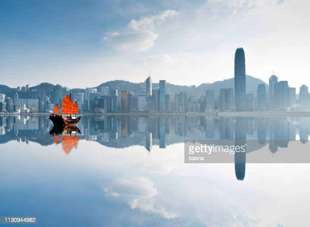 junk boat crossing hong kong harbor - east asia stock pictures, royalty-free photos & images