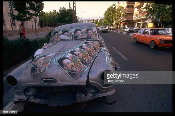 Junked old car plastered w. Presidential election campaign posters picturing moderate cleric Mohammed Khatami, surprise front-runner on street.