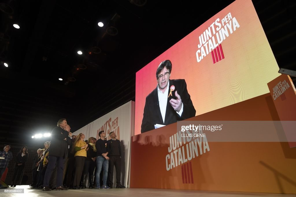 'Junts per Catalonia' (All for Catalonia) grouping cadidate for the upcoming Catalan regional election, Carles Puigdemont, appears on a screen to take part in the campaign opening meeting in Barcelona, on December 4, 2017. Catalans remain deeply split on independence, and several polls suggest pro-secession parties might struggle to win enough seats to form a new regional government after the December 21 regional election. GENE