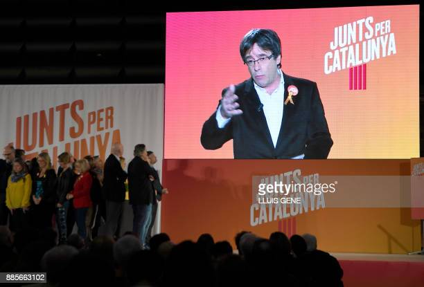 'Junts per Catalonia' grouping cadidate for the upcoming Catalan regional election Carles Puigdemont appears on a screen to take part in the campaign...
