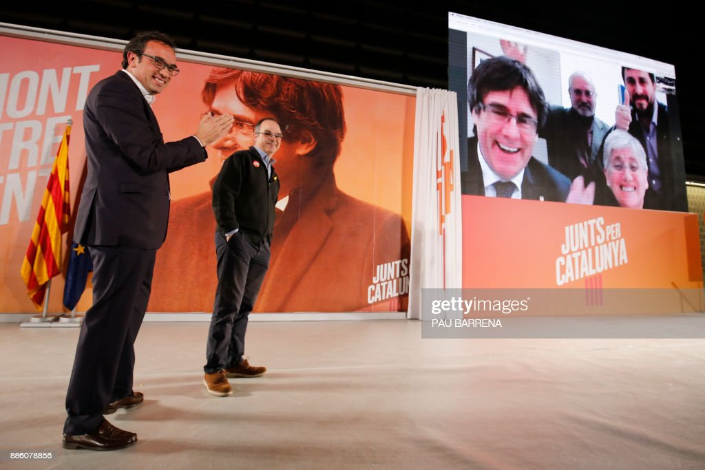 'Junts per Catalonia' (All for Catalonia) grouping candidates for the upcoming Catalan regional election, deposed Catalan regional government spokesperson Jordi Turull (L) and deposed Catalan regional government Territory and Sustainability chief Josep Rull take part in a press conference in Barcelona, while the leading candidate, deposed Catalan regional president Carles Puigdemont and other former ministers participate via viadeo-conference from Brussels, on December 5, 2017. Spain has withdrawn a European arrest warrant for Catalonia's sacked leader Carles Puigdemont and four of his former ministers, who fled to Belgium after the regional parliament declared unilateral independence, the Supreme Court said today. BARRENA