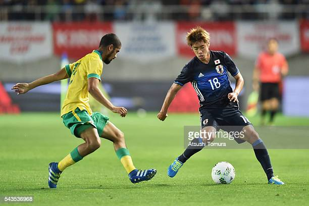 Junya Ito of Japan and Abbubaker Mobara of South Africa compete for the ball during the U23 international friendly match between Japan and South...