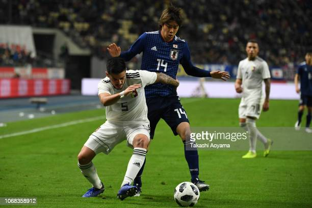 Junya Ito of Japan and Junior Moreno of Venezuela compete for the ball during the international friendly match between Japan and Venezuela at Oita...