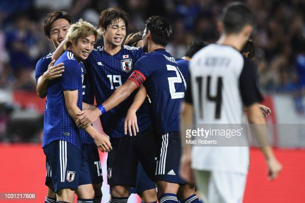 Junya Ito of Japan celebrates scoring a goal with team mates during the international friendly match between Japan and Costa Rica at Suita City...