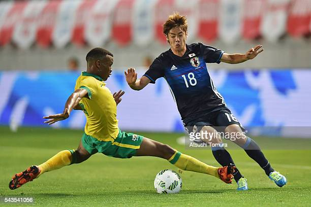Junya Ito of Japan is challenged by Mothiba Mvalo of South Africa during the U23 international friendly match between Japan and South Africa at the...