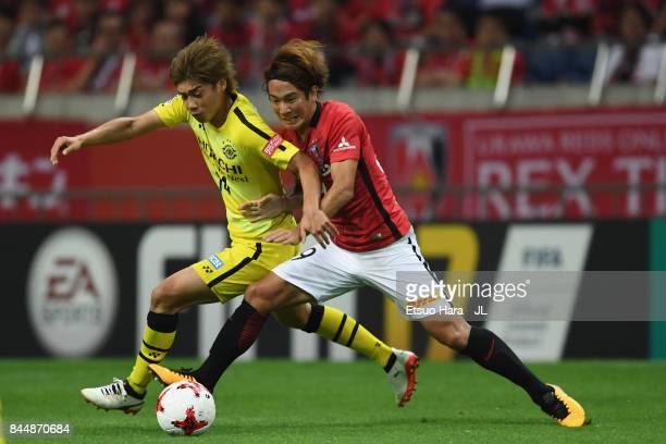 Junya Ito of Kashiwa Reysol and Shinya Yajima of Urawa Red Diamonds compete for the ball during the JLeague J1 match between Urawa Red Diamonds and...
