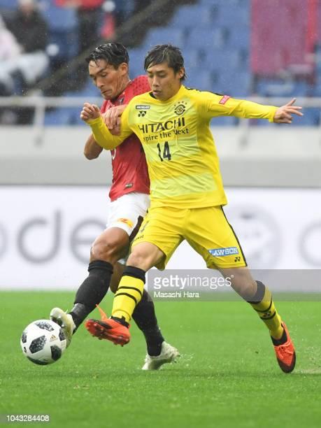 Junya Ito of Kashiwa Reysol and Tomoaki Makino of Urawa Red Diamonds compete for the ball during the JLeague J1 match between Urawa Red Diamonds and...