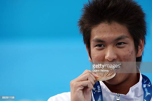 Junya Koga of Japan receives the gold medal during the medal ceremony for the Men's 100m Backstroke Final during the 13th FINA World Championships at...