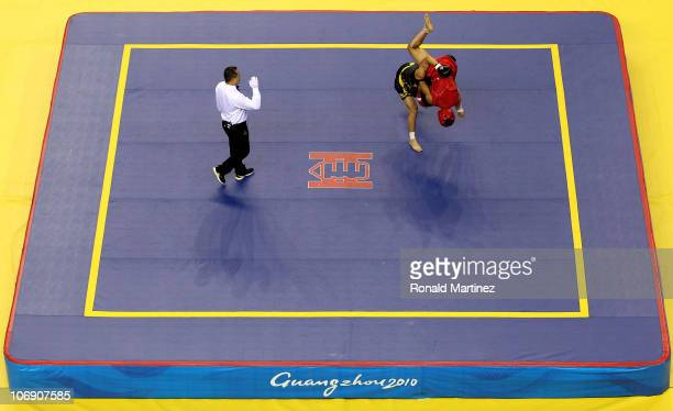 Junyong Zhang of China takes down Mark Eddiva of the Philippines during the men's Sanshou 60kg Wushu at Nansha Gymnasium during day four of the 16th...