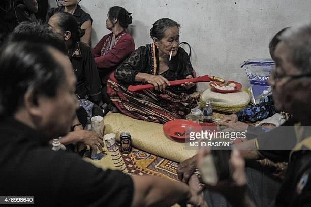 Jupirin Gombur a shaman from the KadazanDusun tribe smokes as she holds a dagger called hulu karis after the Monolibabow rituals in Damat in the...