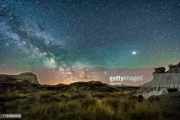 Jupiter at right and the Milky Way rising at left over Dinosaur Provincial Park Alberta May 14 2018 A green band of airglow colours the sky at right...