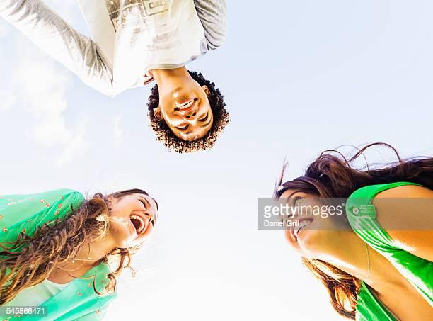 USA, Jupiter, Florida, Upward view of friends (14-15) laughing